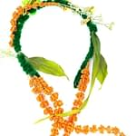 Velvet wrapped headband with long orange flowers dangling from both sides. Leaves and yellow flowers throughout headband.