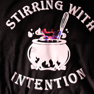 """Tank top with """"stirring with intention"""" surrounding a cauldron boiling with brew"""