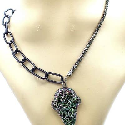Hanging view of glitter infused black resin scooped ice cream pendant with black rhinestone chain on right and black chain on left.
