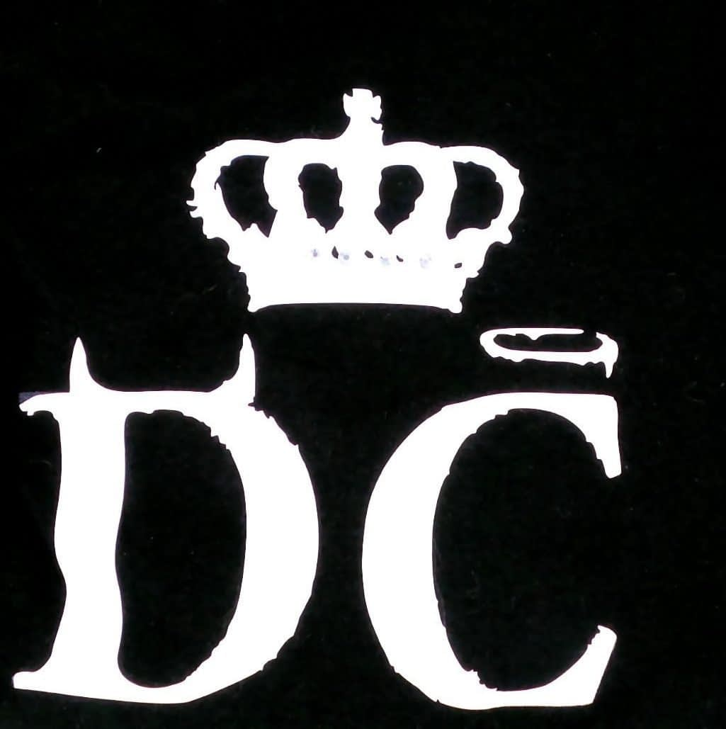 Closeup of logo tee graphic - a D with horns, a C with a halo and a crown above both letters. Rhinestone accents on crown.