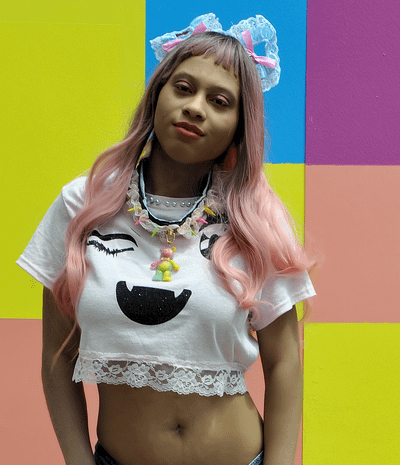 Brown girl wearing lace cat ears, cropped pink tee with lace trim featuring fanged winking Anime eyes and teddy bear choker in front of colorful background.