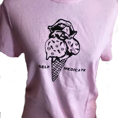 Pink shirt with woman liking lips with ice cream covered with pills in cone. Words Self medicate on each side.