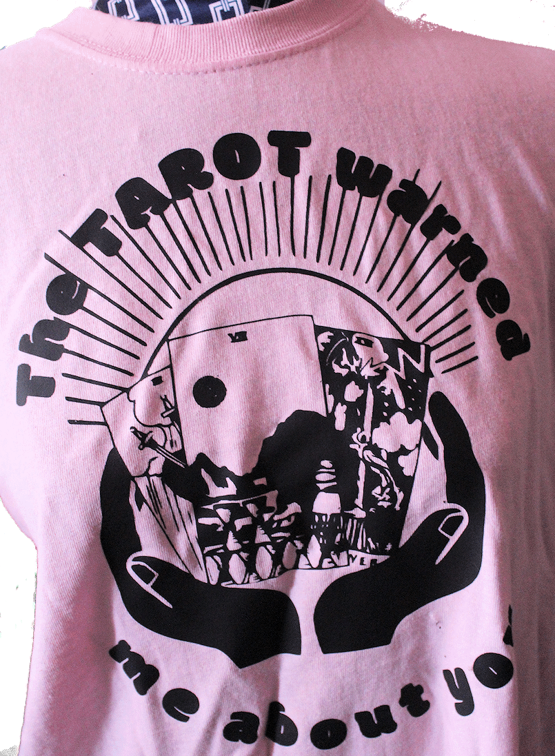 """Closeup of pink tee with words """"the tarot warned me about you"""" surrounding a tarot Spread of 7 of cups, 3 of Swords and the tower cupped in a hand silouhette. Rays come out of spread."""