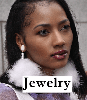 Columbian girl wears large white feather ball stud earrings