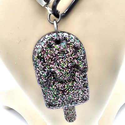 Close of black resin popsicle pendant infused with glitter.