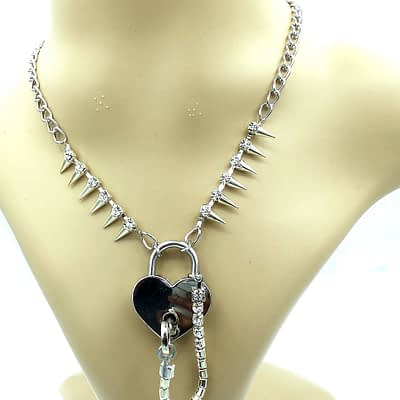 Hanging view of silver heart shaped padlock necklace with silver chain and spiked rhinestone chain.