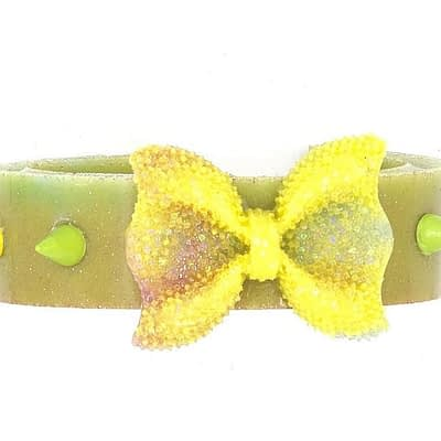 Green acryilic bracelet with yellow and green spikes and bow in center.