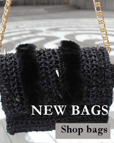 Raffia handbag with spikes and vegan fur is dangled from its gold chain strap.