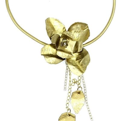 Brass tube curved into necklace with fabricated brass orchid, brass leaves and rhinestone chain.