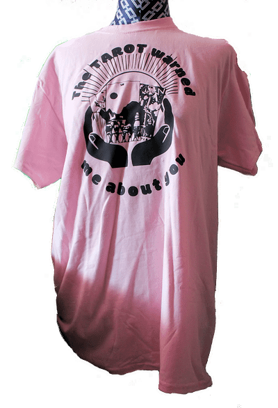 Full length pink tee shirt with tarot graphic of hand holding a tarot spread featuring 3 of swords, 7 of cups and the tower cupped in a woman's hand.
