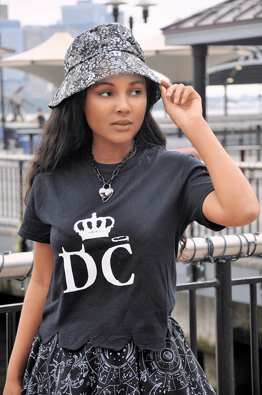 Brown girl wearing dark floral bucket hat and logo tee with scalloped edges.