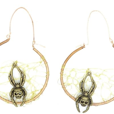 """Copper Hoop earrings with brass wire crocheted in center resembling a web. Spider with skull detail rested on brass """"webs""""."""