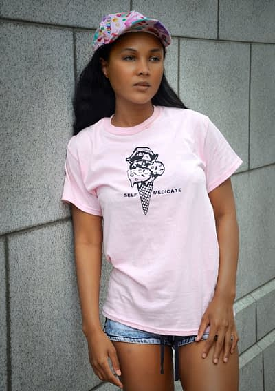 """Black girl wears pink tee with graphic of Ice Cream cone with pills and words """"self-medicate"""""""